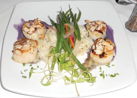 Seared sea scallops with a blackberry brandy reduction are paired with jasmine rice and sautéed vegetables.