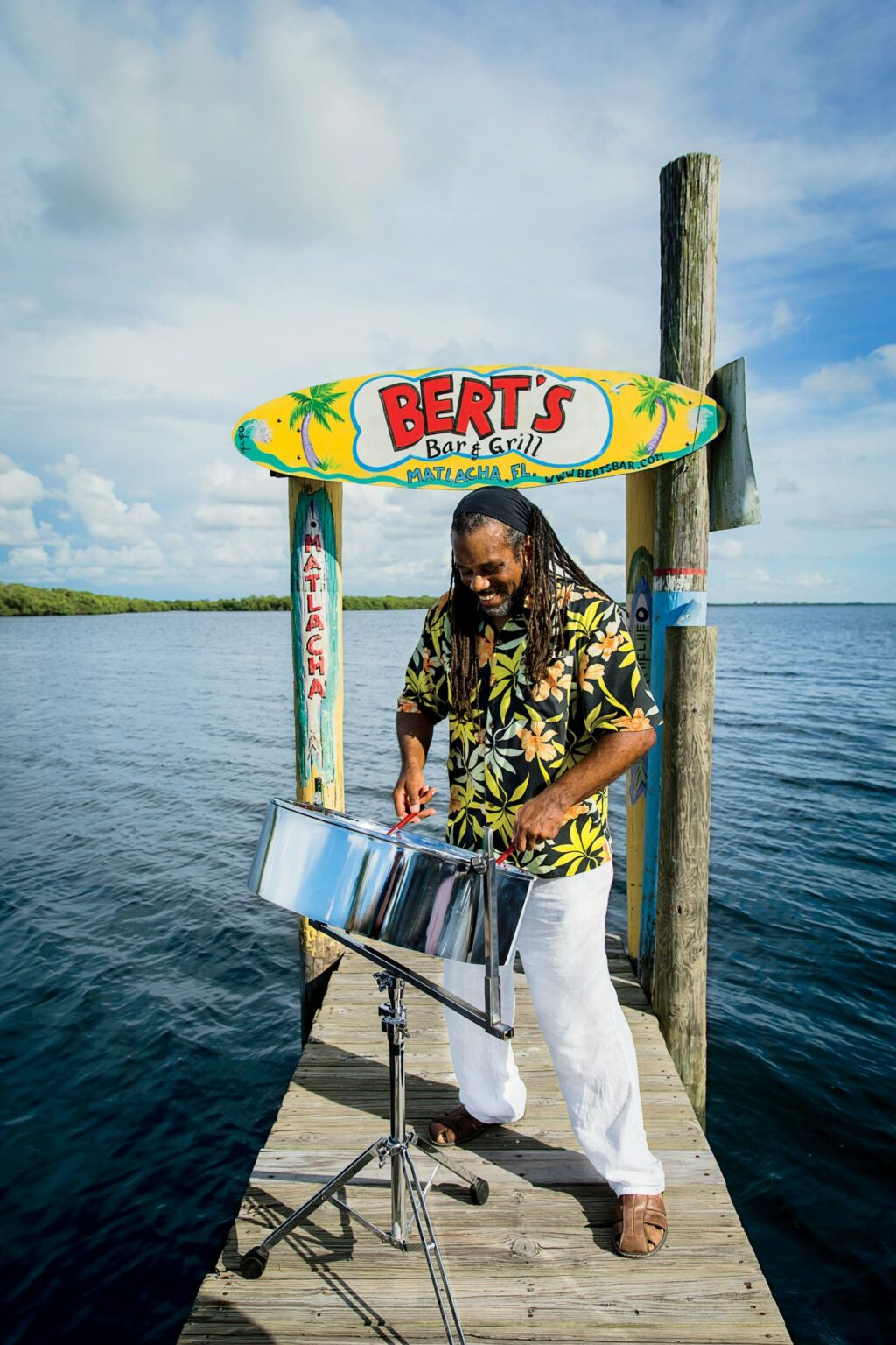 Smiling man plays kettle drum on the dock at Bert's Bar and Grill
