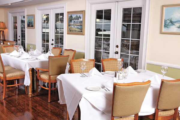 Antique wooden floors and set tables with beautiful white tablecloths and fine table settings: The Dining Room at The Tarpon Lodge