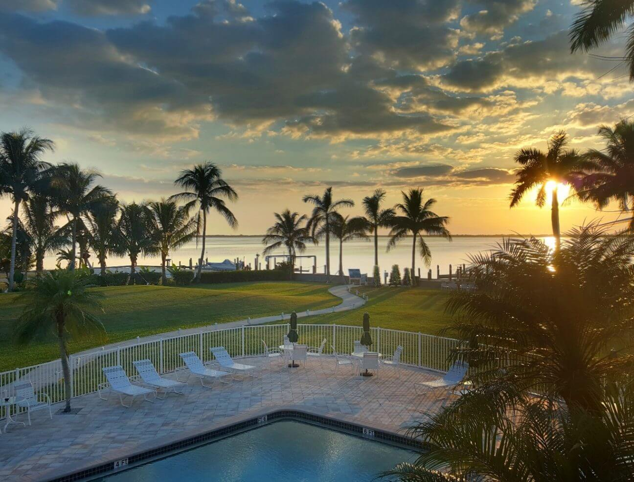 Balcony view of Tarpon Lodge overlooking the pool, the lawn, and the distant waterfront at sunset.